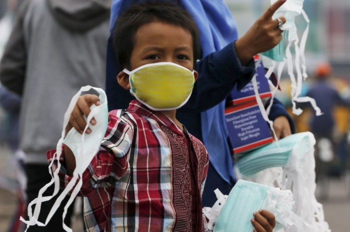 A child offers face masks to people along a haze shrouded street in Palembang, on the Indonesian island of Sumatra, September 20, 2015. Indonesia will take 30 days to bring smouldering forest fires under control, the national disaster management agency said on Friday, as smog from the fires pushes pollution in Southeast Asia to record highs. REUTERS/Beawiharta
